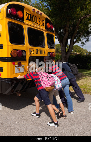 Students Pushing The Back Of The School Bus - Stock Photo