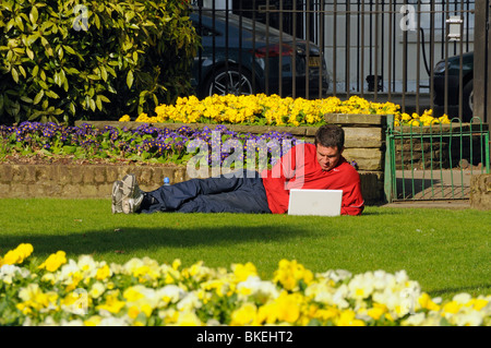 Man laying on grass outside working on laptop in spring sunshire with flowers Canonbury Square Islington London - Stock Photo
