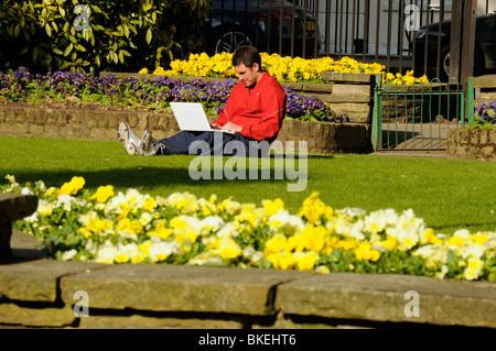 Man working outside on laptop in sunshine with spring flowers, Canonbury Square Islington London England UK - Stock Photo