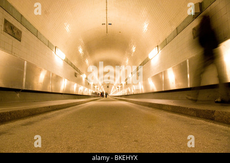 People walk through the Elbe Tunnel (Alter Elbtunnel) in Hamburg, Germany. - Stock Photo