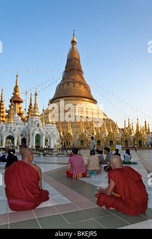 Buddhist monks praying. Shwedagon Paya. Yangon. Myanmar - Stock Photo