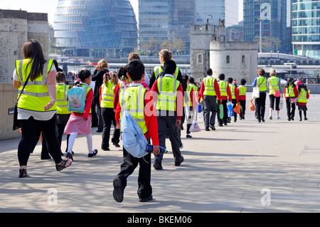 School trip pupils and adults wearing high visibility jackets on visit  to The Tower of London - Stock Photo