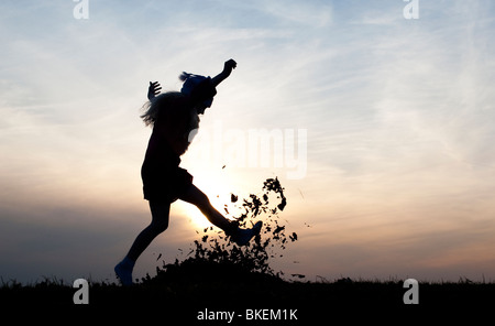 Young Girl energetically having fun kicking a pile of leaves. Silhouette - Stock Photo