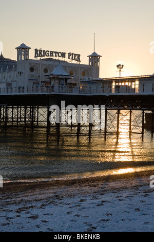Brighton royal pier with sun shining underneath and snow on the beach JPH0264 - Stock Photo