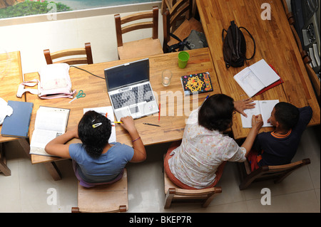 Teacher and two pupils busy doing homework in an orphanage in Medellin, Colombia, South America. - Stock Photo