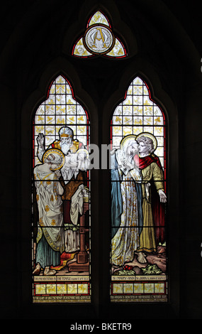 Stained glass window depicting the Presentation of Jesus at the Temple and the Apostle John taking Mary, into his - Stock Photo