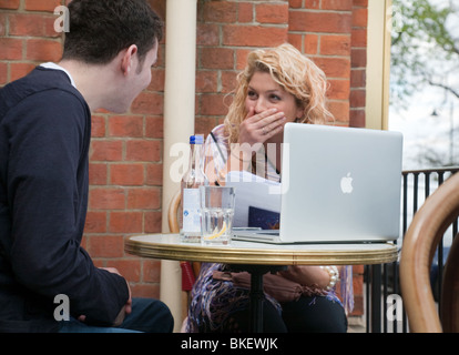 two teenagers, boy and girl with laptop, sitting and talking  in a cafe UK - Stock Photo