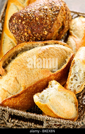 Various kinds of fresh baked bread in basket - Stock Photo