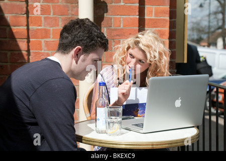 two teenagers,  boy and girl with laptop, sitting in a cafe UK - Stock Photo