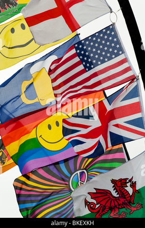 Bright colourful flags including a union jack, american flag, welsh flag and a smiley face rainbow flag flapping - Stock Photo