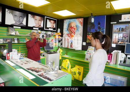A teenage girl having her photo taken in Snappy Snaps photographers, Bond Street branch, London, UK - Stock Photo