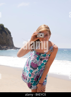 Teenage girl taking picture at beach - Stock Photo