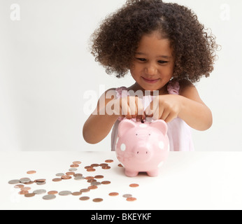 Young girl putting money in piggy bank - Stock Photo