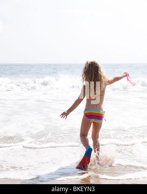 Girl splashing in waves - Stock Photo
