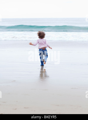 Girl running towards ocean - Stock Photo
