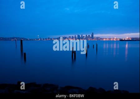 Seattle skyline from West Seattle at sunrise with pilings along Elliott Bay shoreline Seattle Washington State USA - Stock Photo
