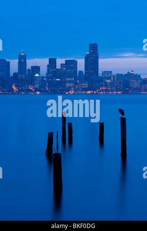 Seattle skyline from West Seattle at sunrise with pilings along Elliott Bay Seattle Washington State USA - Stock Photo