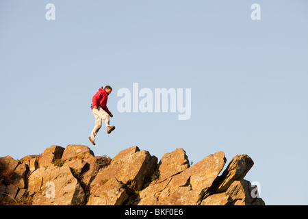A climber jumping on a ridge above Chapel Stile in the Langdale Valley in the Lake district, UK - Stock Photo