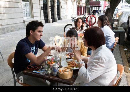 upscale Mexican mother with handsome young adult son & daughter eating pasta at sidewalk cafe in Roma district of - Stock Photo