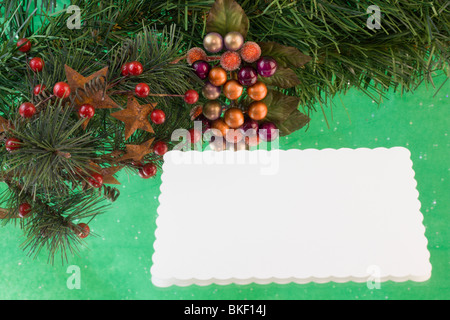 blank Christmas card with fir branch, stars, holly berries on a green reflective background with copyspace - Stock Photo