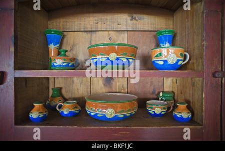 Brilliant blue Mexican pottery graces an antique wood cupboard, in the ski resort town of Ruidoso, New Mexico. - Stock Photo