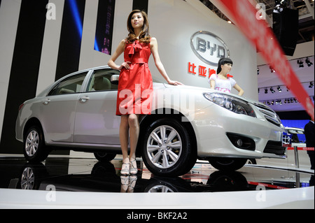 Models pose next BYD L3 sedan at the Beijing Auto Show. 24-Apr-2010 - Stock Photo