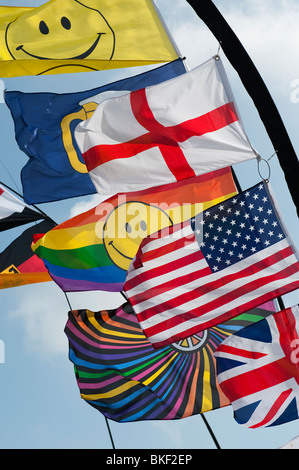 Bright colourful flags including union jack, american flag and george cross flapping in the wind. UK - Stock Photo