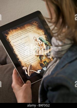 Woman enjoying Alice in Wonderland on the Apple iPad touchscreen computer overshoulder - Stock Photo