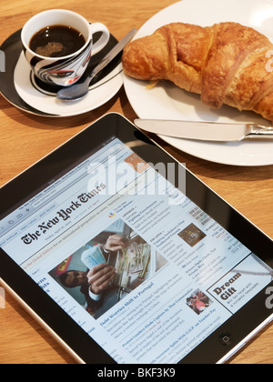 Reading the New York Times at breakfast, on an Apple iPad portable touchscreen tablet computer - Stock Photo