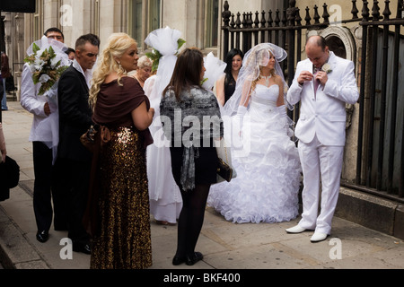 Friends and family of a bride and grooms white wedding gather outside St. Dunstan-in-the-West church before ceremony - Stock Photo