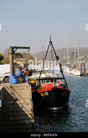 Off loading fish stocks on the quay at Dartmouth south Devon England UK The blue barrels contain seawater stored - Stock Photo