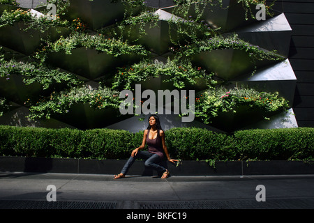 Portrait of a woman sitting outdoors in front of a garden wall. - Stock Photo