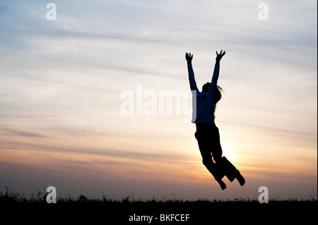 Young Girl energetically having fun jumping around. Silhouette - Stock Photo