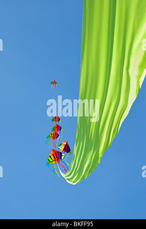 A very colourful kite with six heads and a long, lime green ribbon floating out behind it, taken at the Bristol - Stock Photo