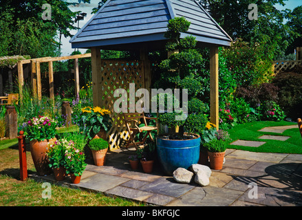 A colourful terraced garden with covered area and planted containers - Stock Photo