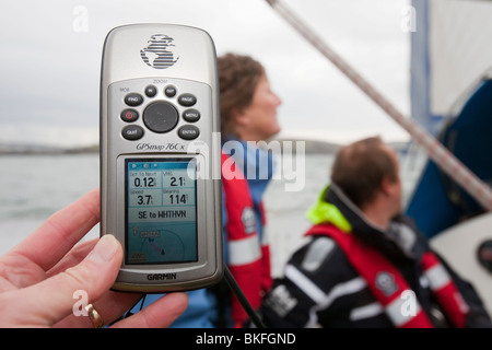 A sailor using a GPS to determine their exact position at sea. - Stock Photo