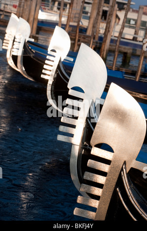 Venice; Evening sun reflecting off steel prows of Gondolas moored on Grand Canal in Italy