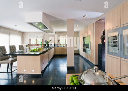 Wooden Kitchens Black Granite Flooring In Large Modern Kitchen With Chairs At Breakfast Bar On Long Peninsular Unit