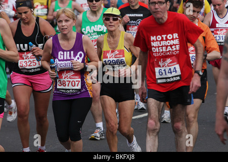 Runners compete in the London Marathon 2010. Photos taken on the north side of the Thames running towards Westminster - Stock Photo