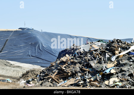 Landfill dump with pile of trash and commercial construction debris with plastic capping  US - Stock Photo
