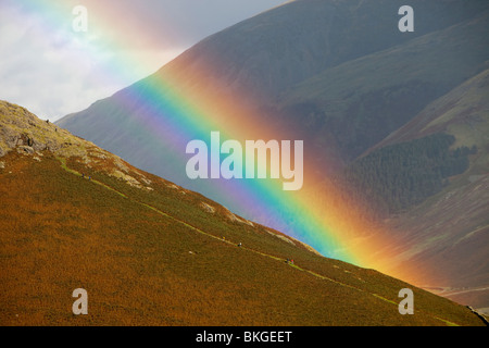 A rainbow arches over Steel Fell and walkers in the Lake District, UK. - Stock Photo