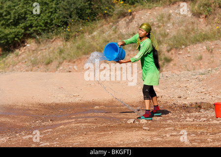 Kyrgyz woman throwing a bucket of water away - Stock Photo