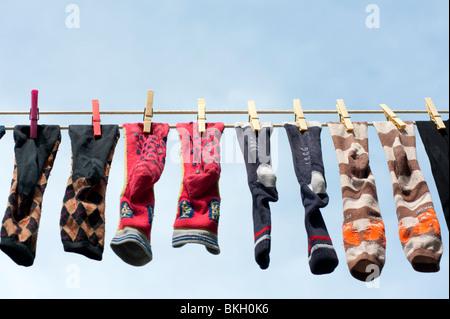 Row of socks drying on washing line in Burano Italy - Stock Photo
