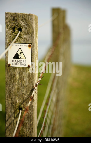 Danger Cliff Edge warning sign on barbed wire fence near Dunstanburgh Castle, Northumberland, United Kingdom. - Stock Photo
