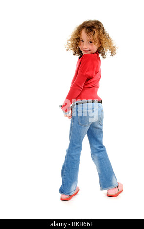 Six year old girl with a loose front tooth wearing blue jeans & a red shirt with sandals poses for the camera - Stock Photo