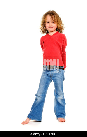 Barefooted six year old girl wearing blue jeans & a red shirt poses for the camera against a plain white background - Stock Photo