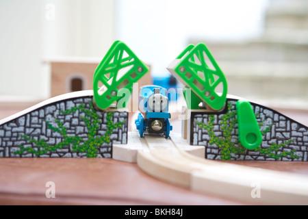 Thomas the Tank Engine going under a toy bridge - Stock Photo