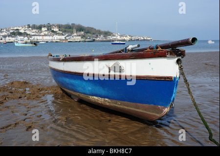 Wooden fishing boat beached at low tide on Instow beach in Devon - Stock Photo