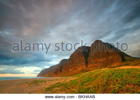 The setting sun lights up several tall mountains above Barking Sands beach in Polihale State Park, Kauai, Hawaii. - Stock Photo