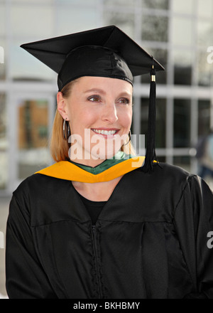 attractive blond woman in graduation cap and gown on campus - Stock Photo